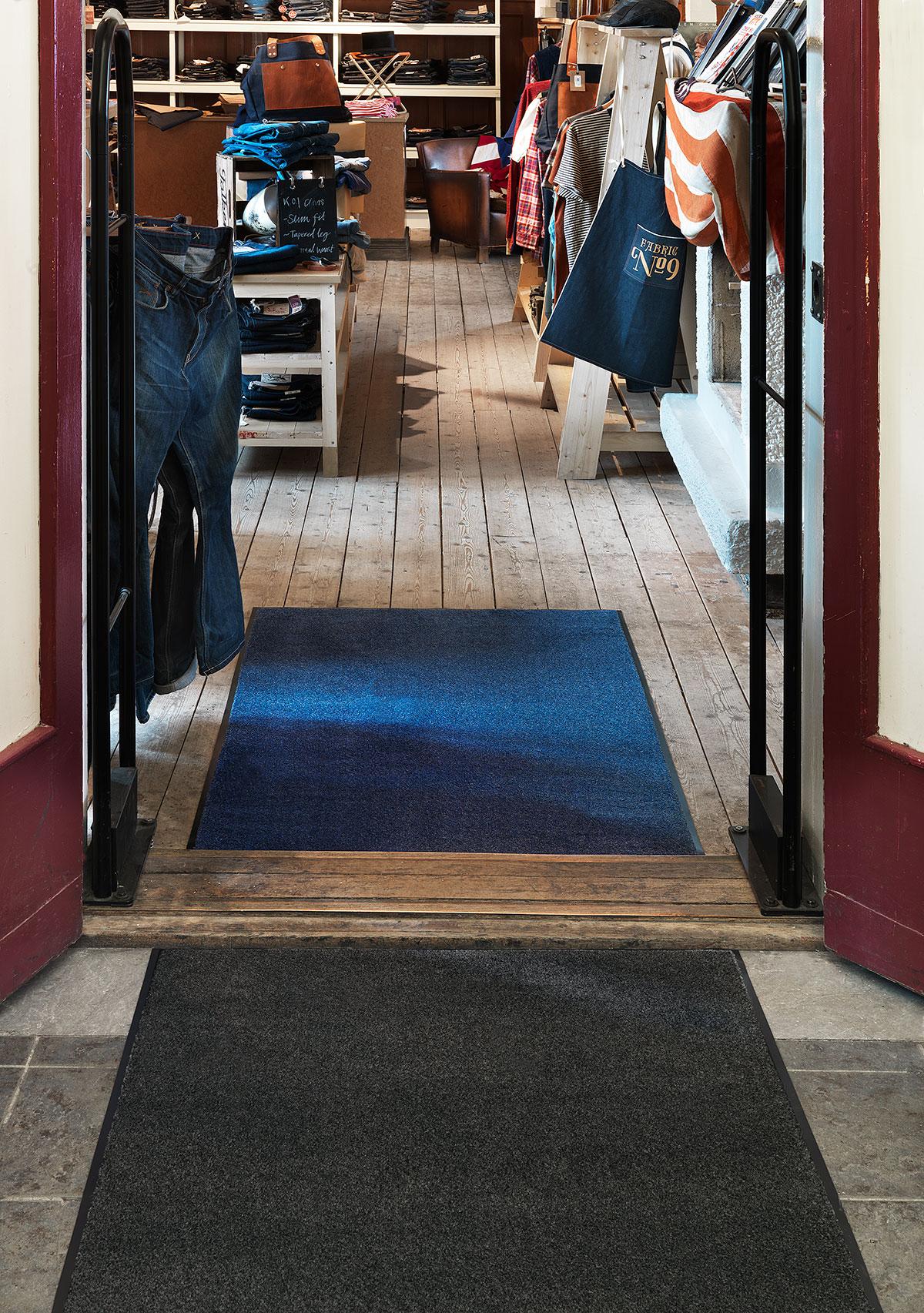 Matting Office Wellness - Torkmatta Solett, blå och grå i en entré till en jeansbutik.